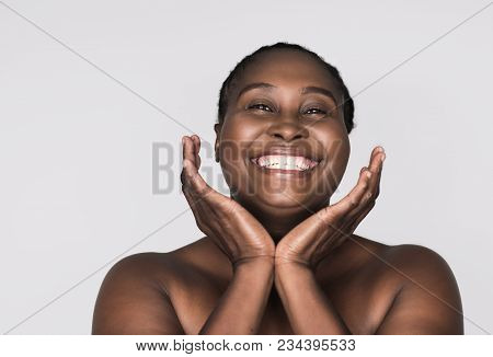 Smiling Young Plus Size African Woman With A Perfect Complexion Framing Her Face With Her Hands Agai