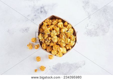 Caramel Popcorn In A Paper Bag On Gray Background. A Place For A Label