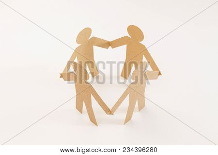 Closed Joining Of Four  Brown Paper Figure In Hand Down Posture On Bright White Background. In Conce