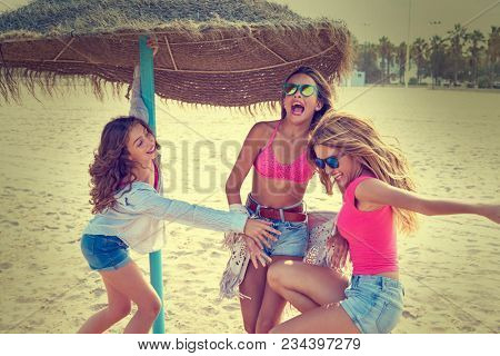 teen best friends girls under thatch umbrella having fun on a beach