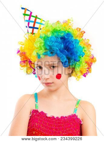 Portrait of little sad girl in clown wig and birthday hat with red spots on her cheeks isolated on white background
