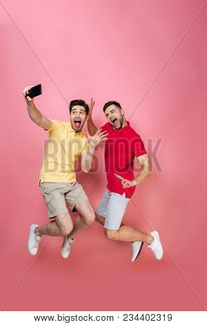 Full length portrait of a joyful gay male couple taking a selfie with mobile phone while jumping isolated over pink background