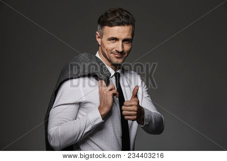 Photo of successful employer in business wear gesturing finger on you while holding jacket over his shoulder isolated over gray background