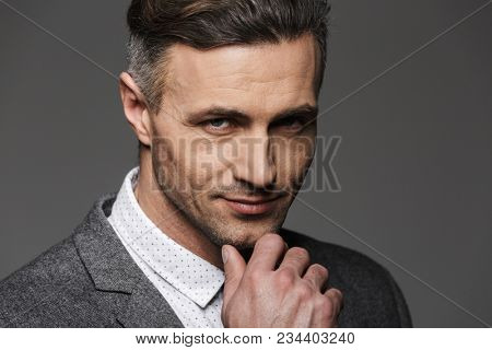 Photo of handsome man wearing business suit looking on camera with meaningful gaze and touching chin isolated over gray background