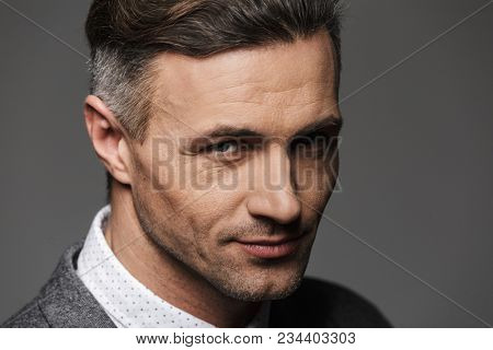 Photo closeup of trendy man wearing business suit looking on camera with meaningful gaze and smile isolated over gray background