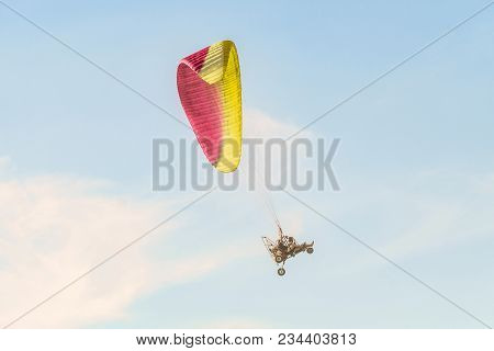 Take-off Of The Motor Paraglider Trike Skyward. Flight On Motor Glider In The Blue Sky.