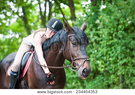 Young Cheerful Teenage Girl-equestrian With Closed Eyes Tenderly Embracing Her Big Lovely Brown Hors