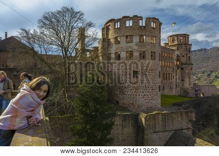 Unidentified Tourists Admire The Beautiful View Of The Heidelberg Castle On The River Side Of Neckar