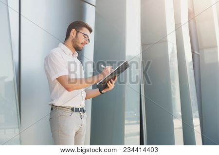 Attractive Pensive Businessman In Eyeglasses Is Holding Clipboard And Making Notes While Standing Ne