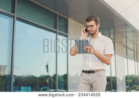 Attractive Concentrated Businessman Is Making A Phone Call And Looking At Digital Tablet Screen Whil