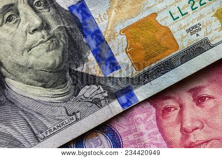 Close Up Of One Hundred Dollar Banknote Over A 100 Yuan Banknote With Focus On Portraits Of Benjamin
