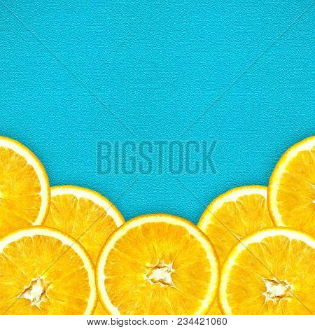 Juicy Cut Oranges On A Bright Blue Background. Oranges Are Located At The Bottom Of The Photo In A S