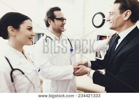 Joyful Businessman Shaking Hands With Doctor Who Cured Ailment. Acknowledgments. Medical Examination