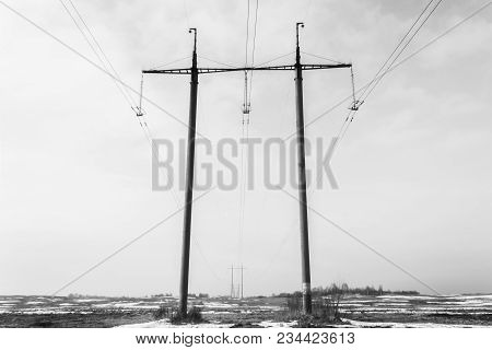 Two Reinforced Concrete Poles Of The High-voltage Transmission Line In The Foreground And Many High-