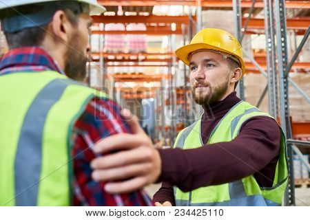 Portrait Of Warehouse Worker Patting His Colleague On The Back Meeting On Break And Chatting
