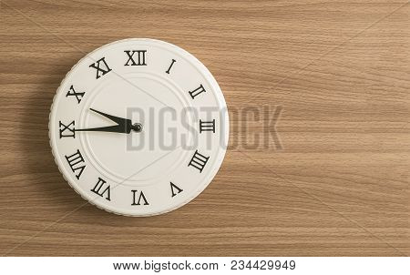 Closeup White Wall Clock For Decorate Show A Quarter To Ten O'clock On Wood Desk Textured Background