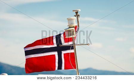 Norwegian Flag On Yacht Ship Mast, Sunny Day Blue Sky Background