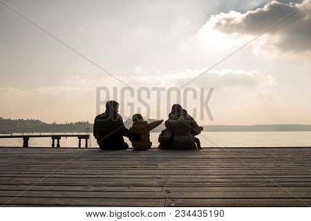 Young Family With Small Children Sitting On A Wooden Deck Overlooking A Tranquil Sea Or Lake At Suns