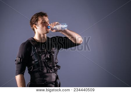 Fit Man Wearing Electro Stimulation Suit Drink Water After Training