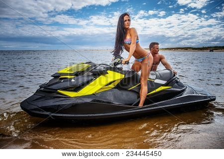 An Attractive Couple Of A Sexy Girl And Shirtless Muscular Male Have Fun With A Jet Ski On A Seacoas