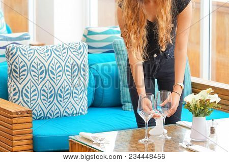 The Waitress Puts Wine Glasses On The Table In The Hotel Restaurant. Lunch Time. The Waitress Serves