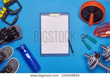 Sport accessories. Boxing gloves, dumbbells, skipping rope, sneakers, wheel exercise, expander  on a blue background.  Top view with copyspace. Fitness, sport and healthy lifestyle concept.