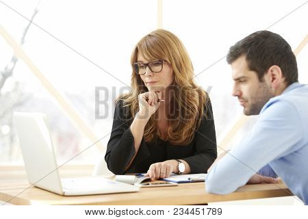 Executive Businesswoman Giving Advice To Young Professional Man