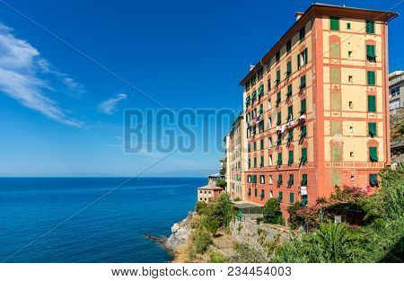 Colorful residential building under blue sky overlooking Mediterranean sea on beautiful sunny day  in small town of Camogli in Liguria, Italy.