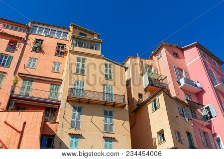 View of colorful residential houses under blue sky in small town of Menton, France.