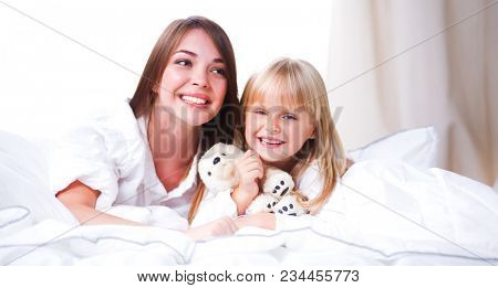 Woman and young girl lying in bed smiling