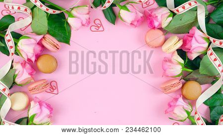 Mother's Day Background Of Pink Roses And Macaron Cookies On Pink Wood Table.