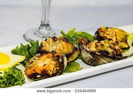 An Appetizer Of Clams Casino Plated On A White Oblong Plate With The Stem Of A Wine Glass In The Bac