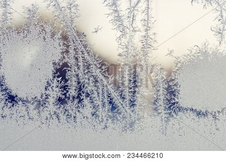 Sunrise Behind A Window With Frost Patterns In The Winter