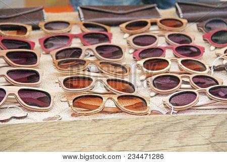 Sunglasses In A Wooden Frame. Many Sunglasses. Designer Glasses.