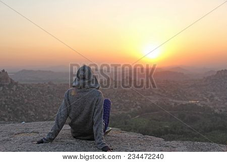 A Girl Sits On A Sunset Or Dawn Background In Hampi, India. Beautiful Sunset Or Sunrise Sun And The