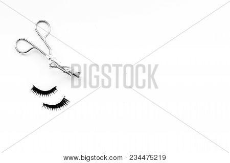 Curled and thick eyelashes. False eyelashes and eyelash curler on white background top view. poster