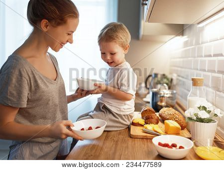 Preparation Of A Family Breakfast. Mother And Baby Son Cook Porridge In Morning