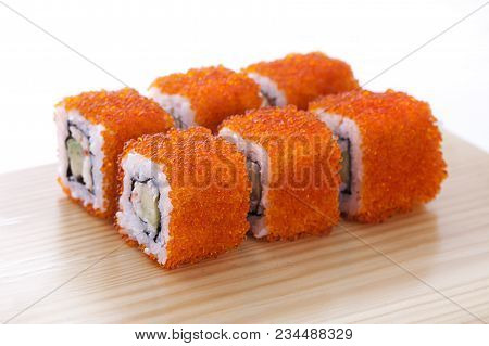 One Set Of California Rolls Covered Orange Tobiko Or Masago Caviar On A Wooden Board On A White Back