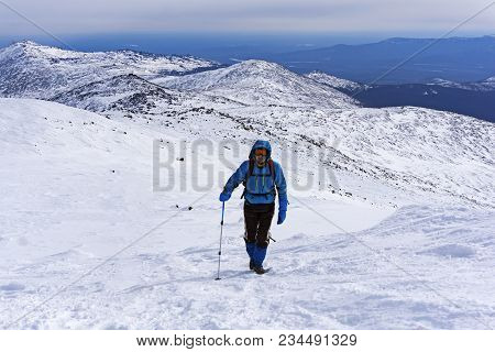 Mountaineer Goes Up The Snow-covered Mountain Slope