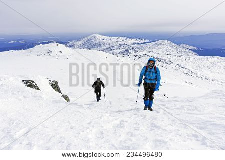Two Mountaineers Goes Up The Snow-covered Mountain Slope