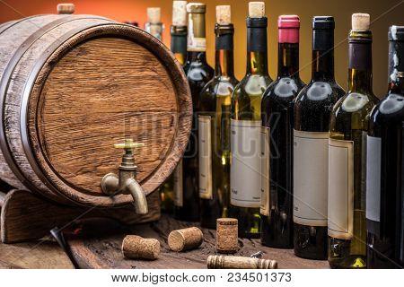Wine bottles in row and oak wine keg. Wine background.