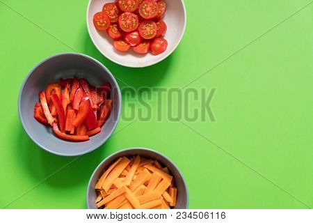 Set Of Vegetables In Plates On A Green Background Red Cherry Tomatoes, Carrots, Sweet Peppers. Recip