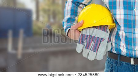 Construction Worker with safety gloves and hat in front of construction site