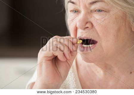 Grandmother Takes A Yellow Pill. Retired Woman.