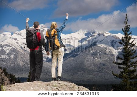 Couple raising their hands on the top of mountains in front of snow-covered mountains