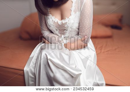 Woman In White Silk Nightgown Suffering From Abdominal Pain While Sitting On Bed In Bedroom At Night