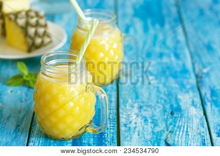Fresh Pineapple Smoothie In Two Glasses On A Blue Wooden Rustic Background. Freshly Blended Summer S