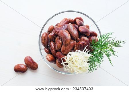 Red Canned Beans In Glass Bowl With Fresh Green Dill And Horse-radish Over White Background