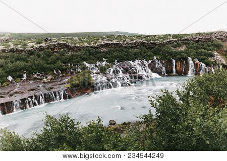 Majestic Landscape With Hraunfossar Waterfalls And Green Vegetation On Hills In Iceland