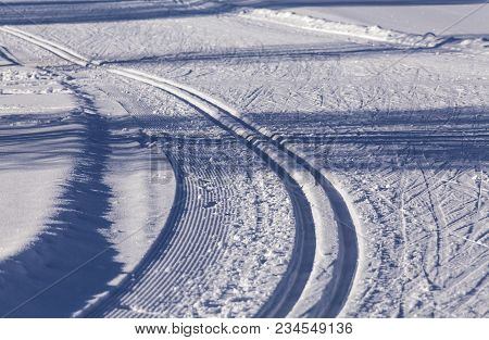 Closeup On Cross-country Skiing Tracks In Winter Landscape. Shadows And Texture.